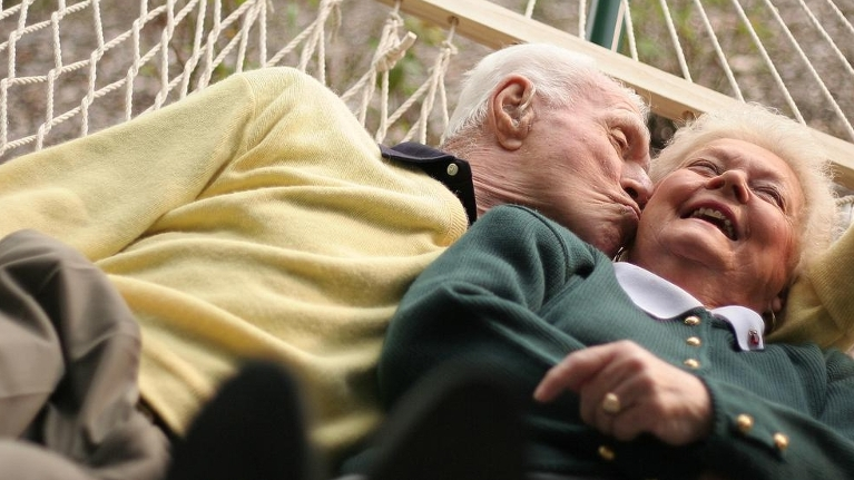 Elderly Couple on a hammock. Man is kissing woman on the cheek